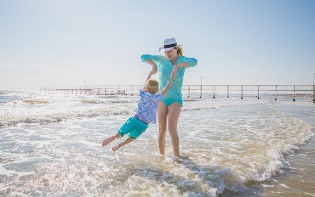 La mamma gioca con suo figlio sulla spiaggia
