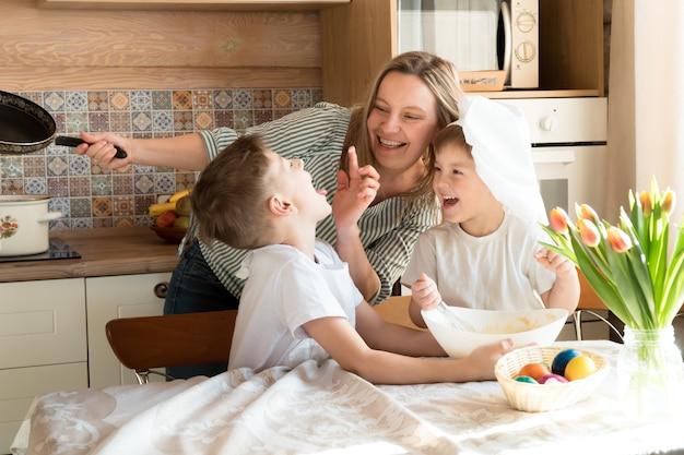 La mamma gioca e cucina la cena di pasqua con i suoi figli a casa in una giornata di sole