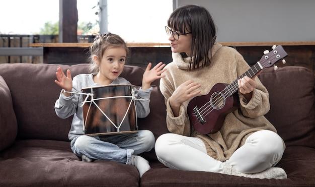 La mamma gioca con sua figlia a casa. lezioni su uno strumento musicale. sviluppo dei bambini e valori della famiglia. il concetto di amicizia e famiglia dei bambini.