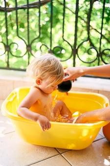 La mamma versa l'acqua su un bambino piccolo seduto in una bacinella sul balcone