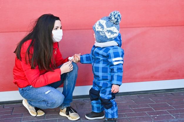 Mamma in una maschera protettiva che scherza con il suo bambino