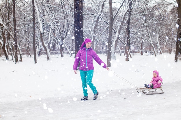 Mamma tira su una figlia da slitta mentre cammina nel bosco