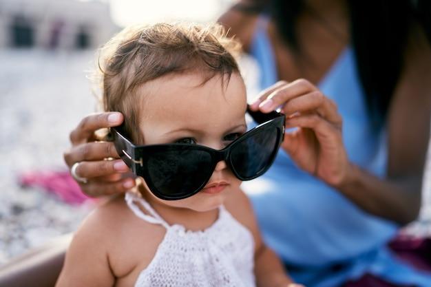 La mamma mette gli occhiali da sole a una bambina
