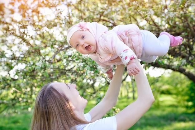 La mamma ha cresciuto sua figlia nelle sue mani sullo sfondo della natura. il bambino è volare. maternità felice.