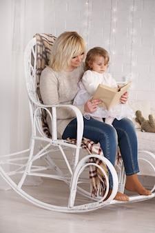 Mamma che legge un libro a una figlia seduta su una sedia di vimini