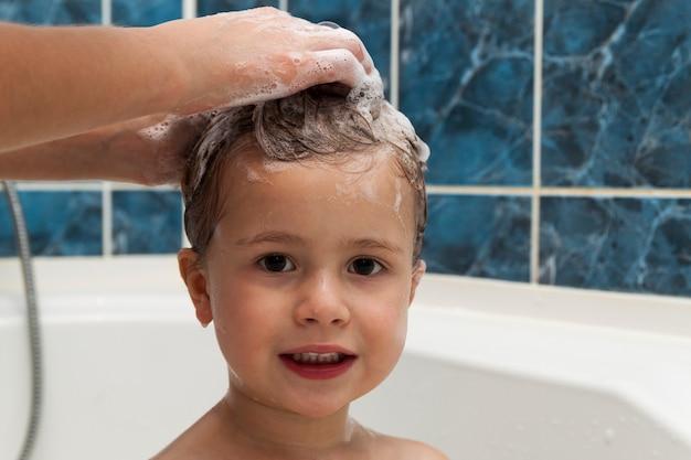 Le mani della mamma lavano la testa della piccola ragazza nel bagno.