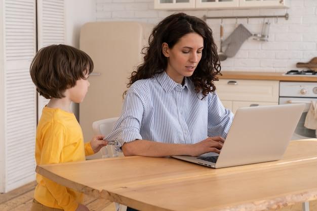 La mamma si siede al tavolo in ufficio durante il blocco lavorando sul laptop e il bambino si distrae e fa rumore