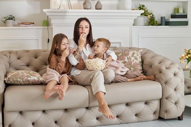 La mamma si siede sul divano con suo figlio e sua figlia e guarda un film. una donna, un ragazzo e una ragazza mangiano popcorn mentre guardano un film. la famiglia sta riposando a casa durante il fine settimana