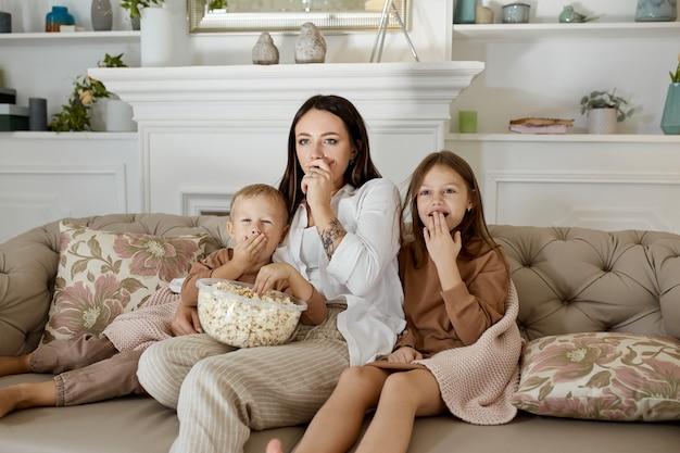 La mamma si siede sul divano con suo figlio e sua figlia e guarda un film. una donna, un ragazzo e una ragazza mangiano popcorn mentre guardano un film. la famiglia riposa a casa nel fine settimana
