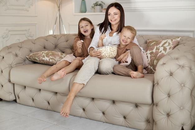 La mamma si siede sul divano con suo figlio e sua figlia e guarda un film