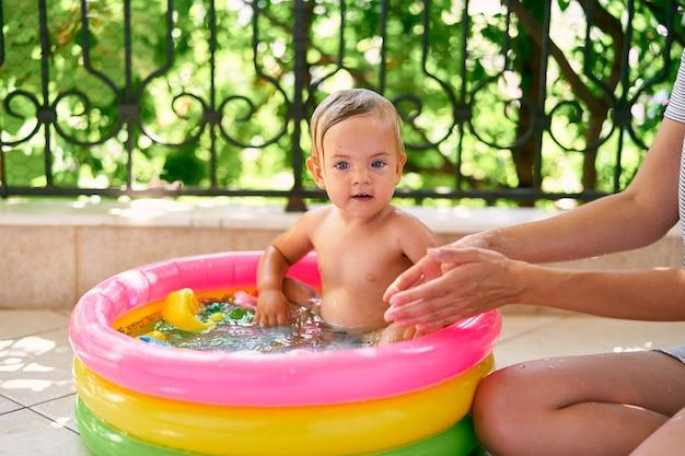La mamma si siede sul pavimento accanto a un bambino in una piccola piscina gonfiabile