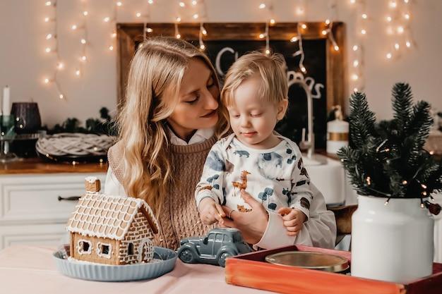 La mamma si siede con il figlio in cucina al tavolo con decorazioni di capodanno con ghirlande, lo tiene tra le braccia e lo guarda.