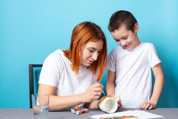 Mamma e figlio sorridono allegramente e dipingono il coperchio in arancione brillante su una superficie blu.