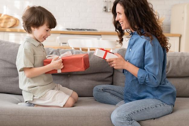 Mamma e figlio festeggiano il compleanno insieme, mamma felice e figlio eccitato si siedono sul divano e tengono i regali sorridendo