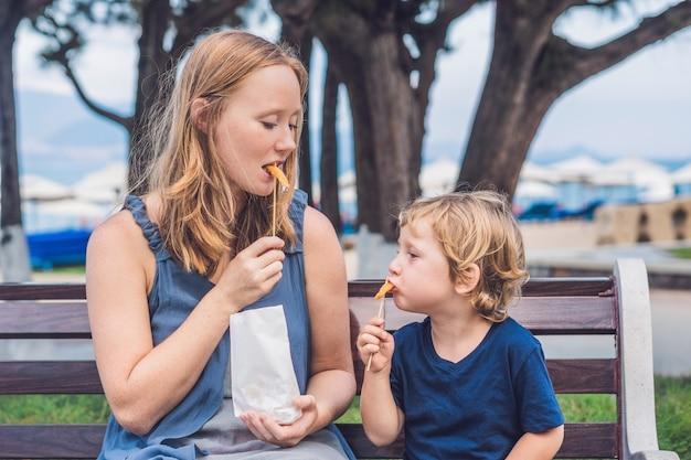 Mamma e figlio mangiano patate dolci fritte nel parco