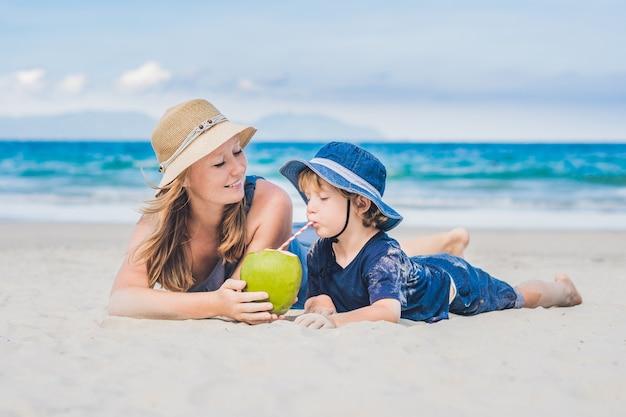 Mamma e figlio si godono la spiaggia e bevono cocco.