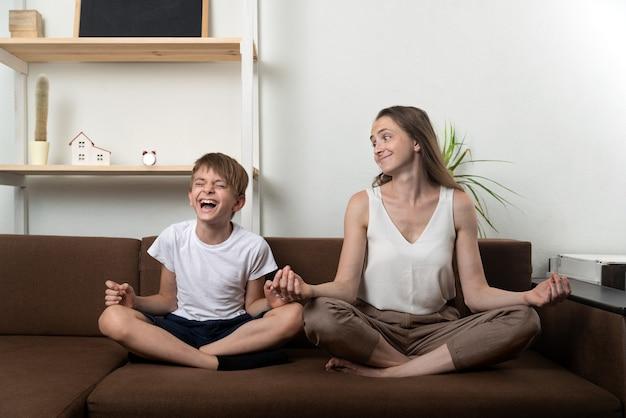 Mamma e figlio si divertono mentre praticano lo yoga seduto sul divano. meditazione a casa con i bambini.