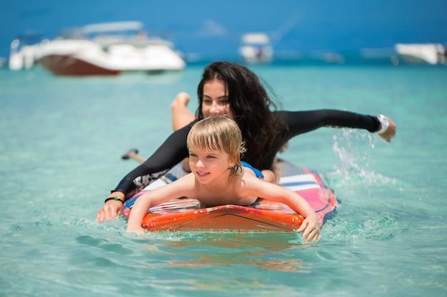 Mamma e figlio fanno surf nell'oceano sulla lavagna