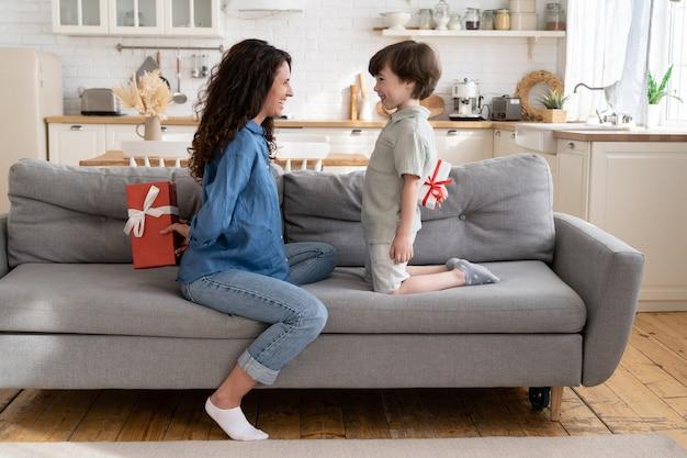 Mamma e figlio nascondono regali pronti per salutare mamma e bambino con il compleanno o il natale delle vacanze in famiglia