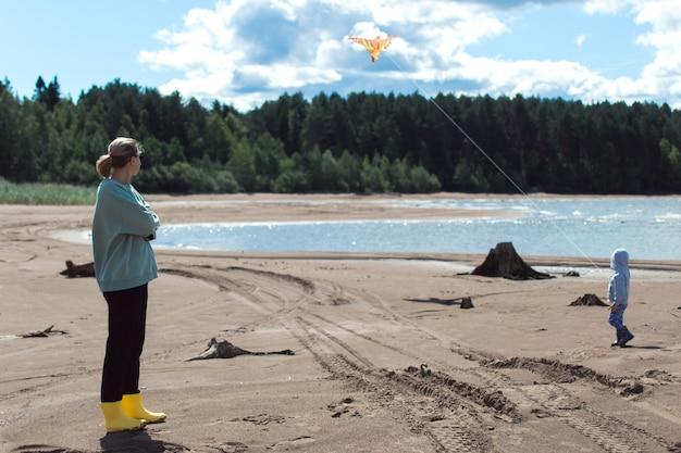 Mamma e figlio giocano con l'aquilone sulla riva del fiume