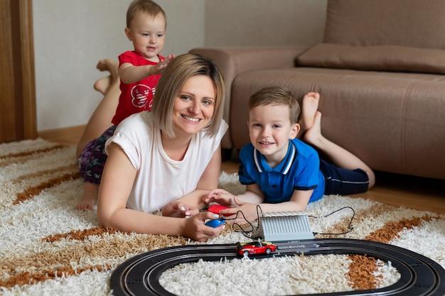 Mamma e figlio giocano a correre sul tappeto e la piccola figlia si siede sulla schiena di sua madre.