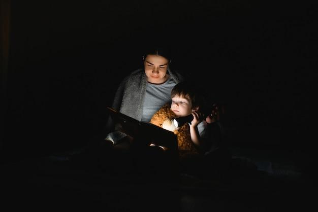Mamma e figlio che leggono un libro con una torcia sotto la coperta