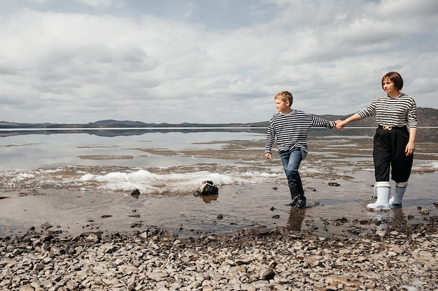 Mamma e figlio sulla riva del fiume. mamma e figlio in canottiera e stivali di gomma corrono allegramente sull'acqua. intimità familiare all'aria aperta. ricreazione e stile di vita.