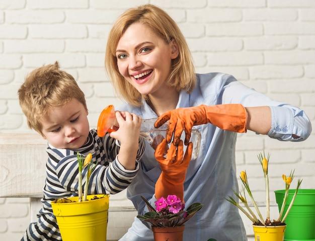 Mamma e figlio insieme a spruzzare fiore di primavera in vaso. il bambino piccolo aiuta la madre a prendersi cura delle piante.