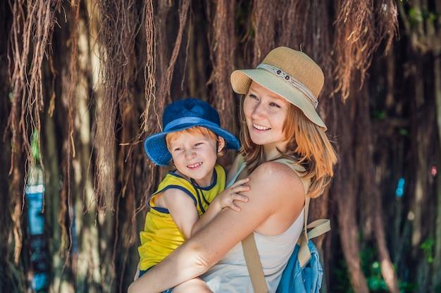 Mamma e figlio in vietnam, i viaggiatori sono sullo sfondo bellissimo albero con radici aeree