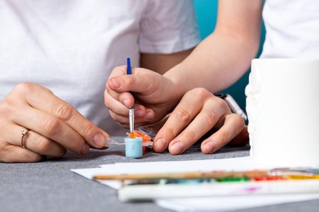 Mamma e figlio in magliette bianche sono impegnati nella pittura, sbriciolano una tazza su uno sfondo blu. imparare le basi del disegno in età prescolare