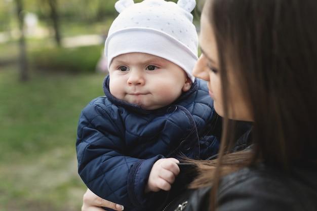 Mamma e figlio con un bambino piccolo stanno camminando in una foresta o in un parco di primavera