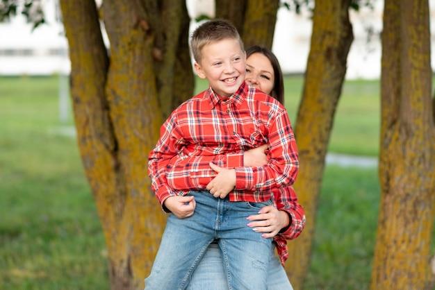 Mamma accovacciata, abbraccia un figlio sorridente. per qualsiasi scopo.