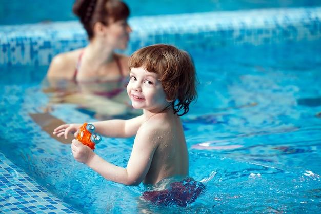 La mamma insegna a un bambino a nuotare in piscina.
