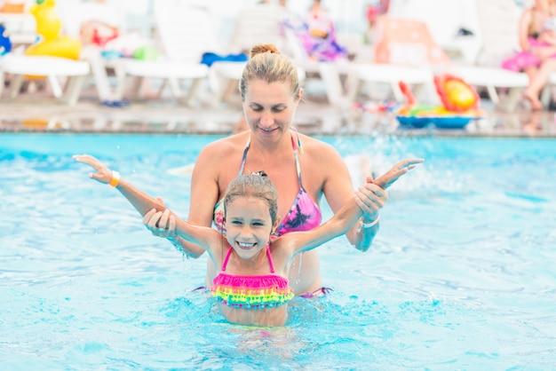 La mamma insegna alla figlia a nuotare in piscina