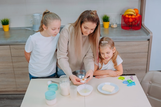 La mamma insegna alle sue figlie a cucinare la pasta in cucina.