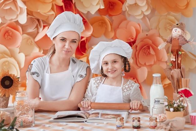 La mamma insegna alla piccola figlia a stendere la pasta. il concetto di genitorialità