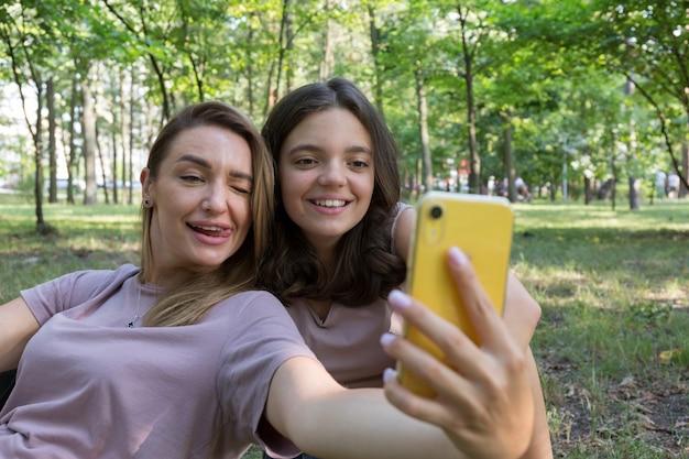 Mamma e figlia adolescente si fanno un selfie mentre camminano in un parco estivo. utilizzo di uno smartphone