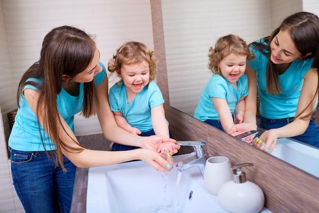 Mamma che lava le mani del bambino