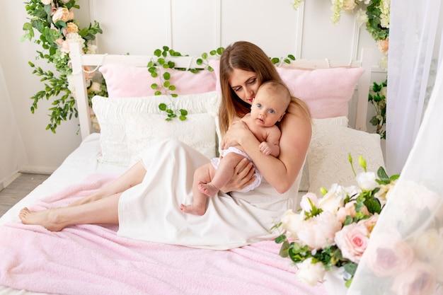 Mamma con bambino in braccio a casa sul letto, il concetto di famiglia e maternità