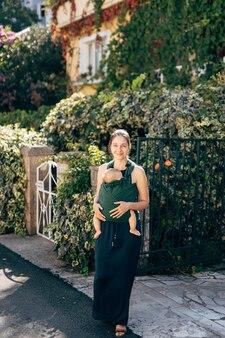 Mamma con un bambino su una fionda vicino al recinto di una casa