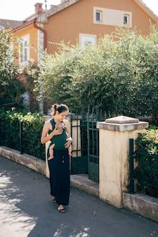 La mamma con un bambino su una fionda cammina per strada oltre il recinto di una casa con il verde
