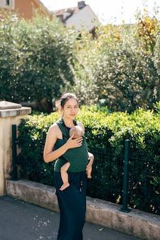 La mamma con un bambino su una fionda cammina per la strada oltre il recinto di una casa