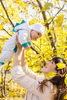 Mamma con un bambino, un bambino cammina in autunno nel parco o nella foresta. foglie gialle, la bellezza della natura. comunicazione tra un bambino e un genitore.