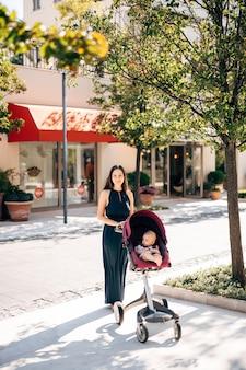 Mamma con bambino in un passeggino in una strada cittadina