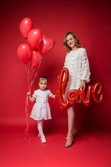 Mamma con amore palloncino sta con sua figlia con una bracciata di palloncini rossi su rosso