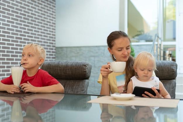Mamma con bambini al caffè. la giovane madre e due bambini bevono caffè e cocktail.