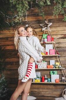 Mamma con una figlia in braccio sullo sfondo del nuovo anno.