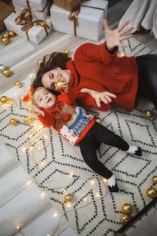 La mamma con la figlia in maglioni caldi rossi sta saltando sul letto. maternità felice. relazioni familiari calde. interni di natale e capodanno. amare. concetto di famiglia.