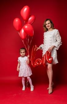 Mamma con un amore di palloncino di alluminio e figlia con una bracciata di palloncini rossi su rosso