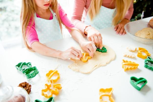Mamma con ragazza che produce biscotti con forme